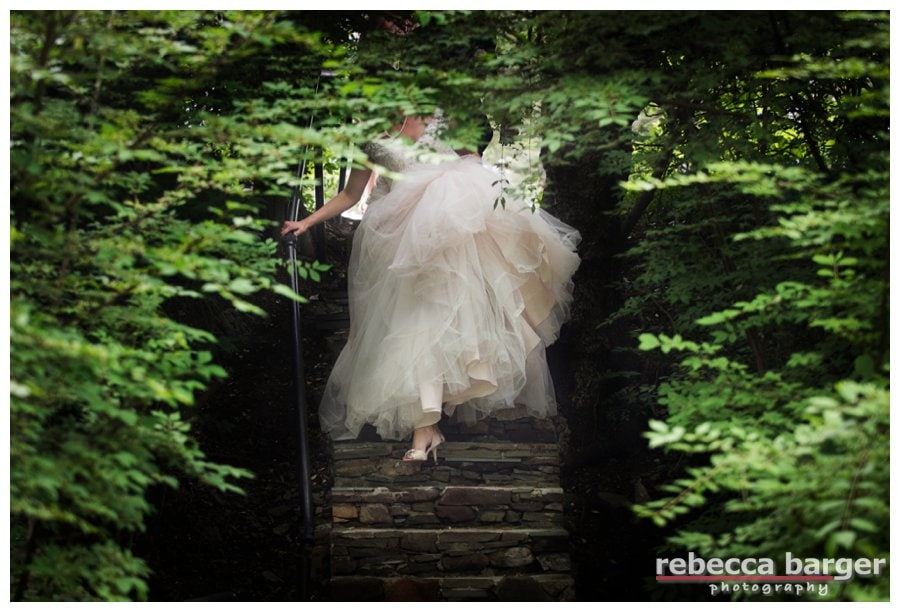 Becca comes down the stairs carrying all of her gown.