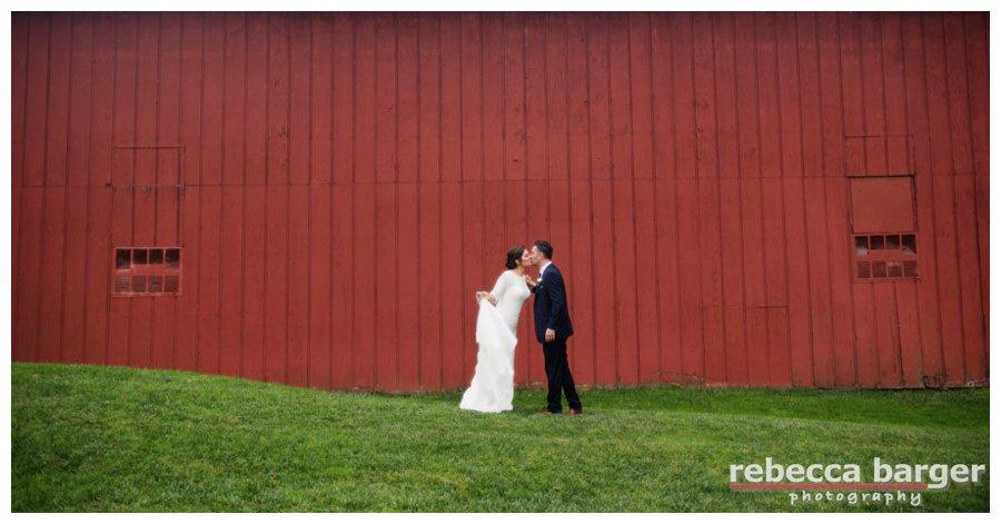 A sweet, little kiss near the barn at The Cricket Club.