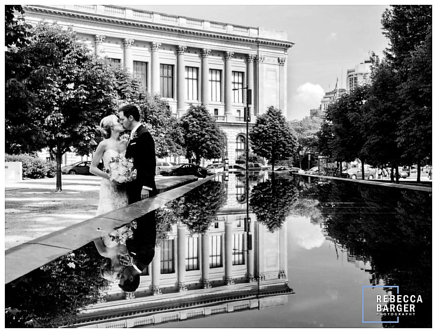Lauren and James share a wedding day kiss as the Philadelphia Free Library is reflected in a fountain pool.
