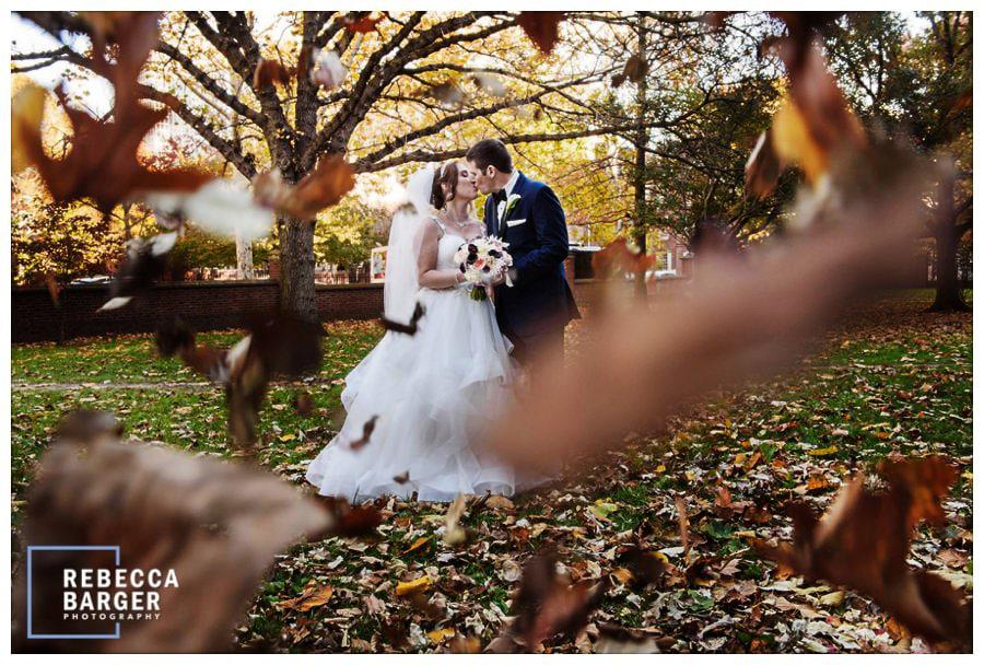 Lauren and Brian, kiss amongst the falling leaves, on their November wedding day, in Philadelphia.